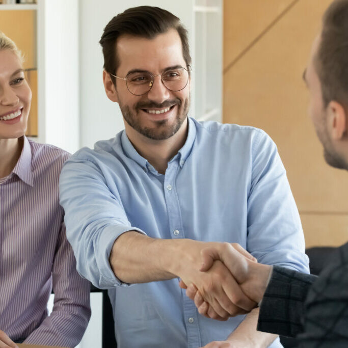 Happy european family couple getting acquainted with financial advisor at office meeting, smiling clients celebrating making agreement or closing, shaking hands with male real estate agent indoors.